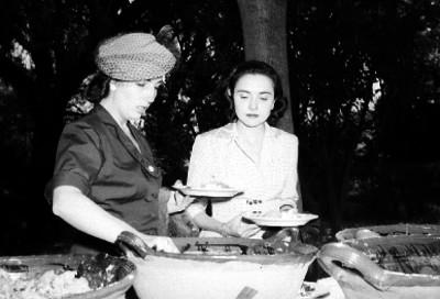 Mujeres elegantes sirviendose de unas cazuelas