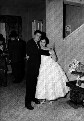 Quinceañera abrazando a un hombre en una habitación, retrato
