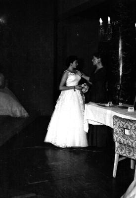 Mujer acomodando el vestido a una quinceañera en una habitación