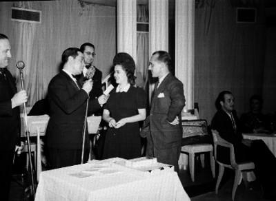 Hombre ante el micrófono y otras personas durante un evento social