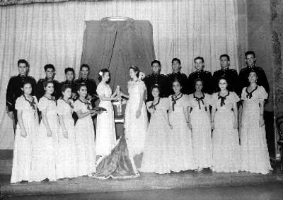Mujer entregando un cetro a una reina de belleza acompañada por si padres y cadetes, retrato de grupo