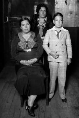 Niño en compañía de dos mujeres en el interior de una casa, retrato de familia