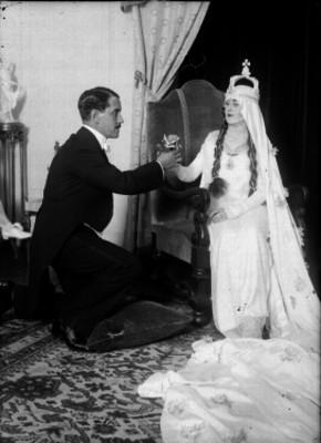 Hombre inclinado ofreciendo una flor a mujer vestida de reyna