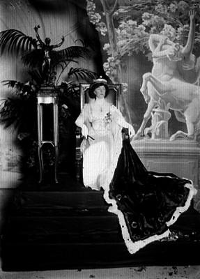 Mujer vestida de reina y sentada en un tronco, retrato