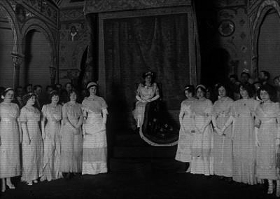Mujer vestida de reina en un tronco y varias damas a su lado, retrato de grupo