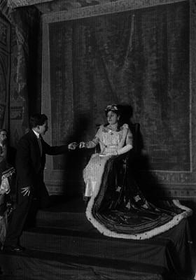 Hombres ofreciendo algo con reverencia a una mujer vestida de reina