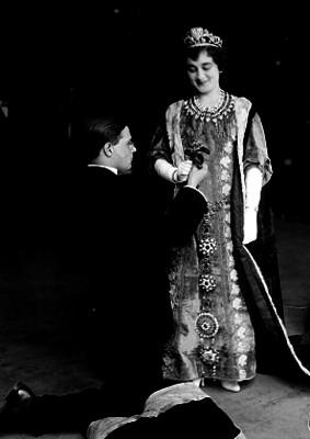 Hombre ofreciendo una flor con reverencia a una mujer vestida de reina