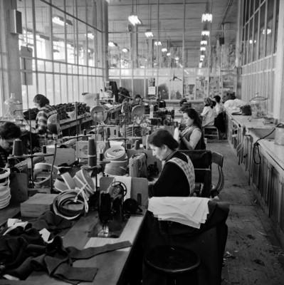 Mujeres utilizan máquinas de coser para hacer gorros