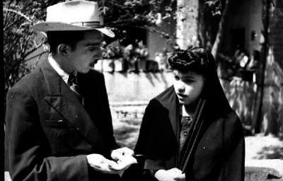 Periodista entrevistando a una mujer en el patio de una casa