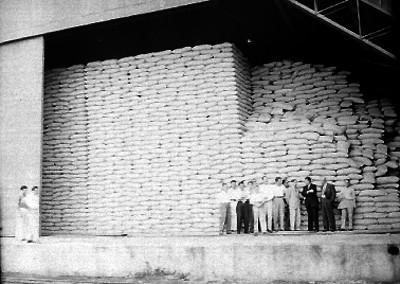 Marco Antonio Muñoz con empresarios en un almacén de azúcar del Ingenio azucarero de Zacatepec, Morelos; retrato de grupo