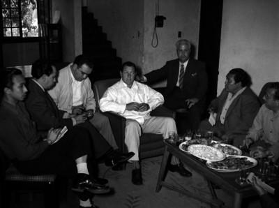 Marco Antonio Muñoz conversando con empresarios y periodistas en una sala