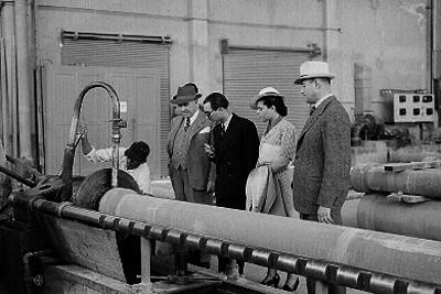 Empresarios y pareja observando a un trabajador manejando una máquina