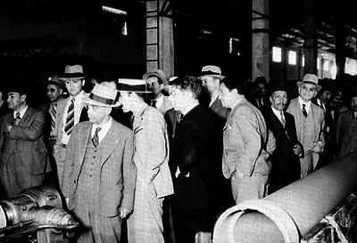 Ferrocarrileros observando la maquinaría industrial de la fábrica Eureka