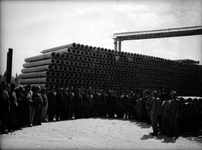 Ferrocarrileros junto a unos tubos de concreto en los patios de la fábrica Eureka, retrato de grupo