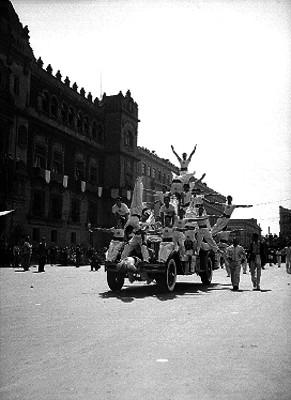 Camión con acrobatas realizando una pirámide durante un desfile