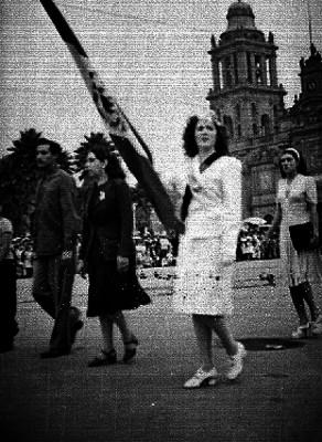 Obrera uniformada portando bandera mexicana durante el desfile de conmemoración del día del trabajo en el zócalo