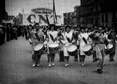 Banda de guerra frente a un contingente de la confederación nacional de trabajadores desfilando durante la conememoración del día del trabajo en el zócalo