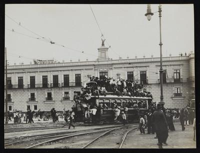 Tranvía con gente frente a Palacio Nacional durante los tumultos por renuncia de Porfirio Díaz