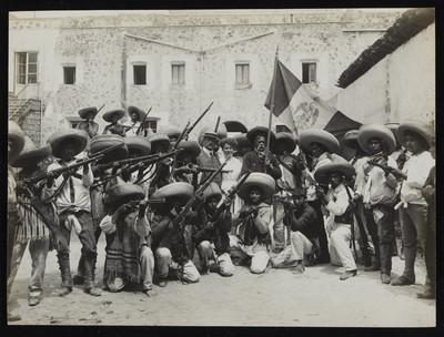 Grupo de zapatistas armados en el patio de un claustro