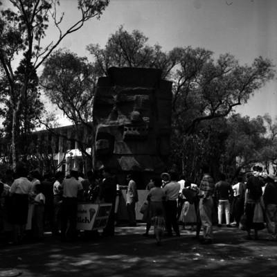 Gente reunida en torno a la escultura de Tláloc a la entrada del Museo Nacional de Antropología e Historia