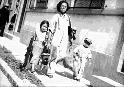 Mujer anciana y dos niños caminando por una calle cargando herramientas