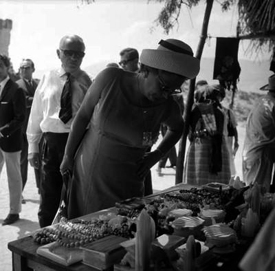 Juliana, reyna de Holanda acompañada de Bernardo, principe de Holanda y su comitiva observando un puesto de artesanías de madera en Mitla