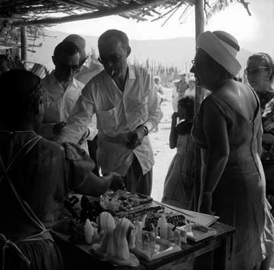 Juliana, reyna de Holanda y Bernardo, principe de Holanda acompañados de su comitiva observando las artesanías de madera en un puesto