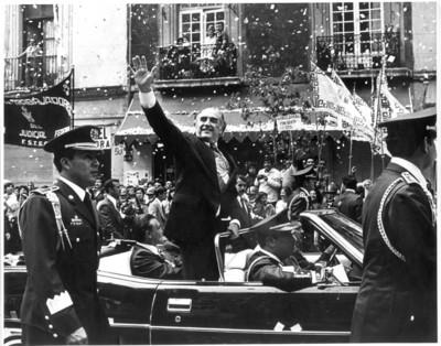 José López Portillo abordo del automóvil presidencial saluda a la gente durante desfile
