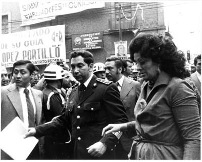 Carmen Romano Nölck camina junto a hombre del Estado Mayor Presidencial