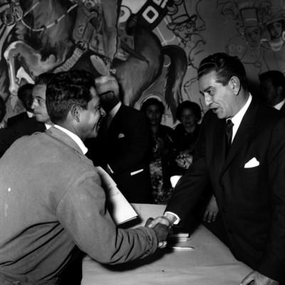Adolfo López Mateos saludando a un hombre, durante una ceremonia