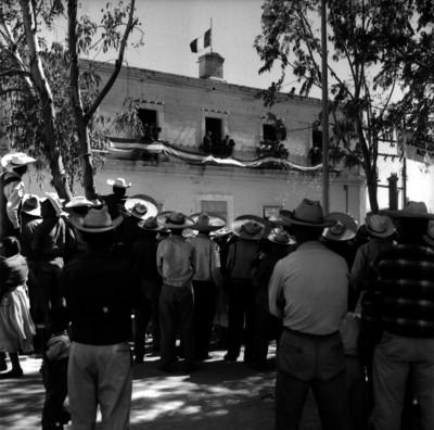 Campesinos en una ceremonia con el presidente Adolfo López Mateos, que se encuentra en un balcón de un edificio