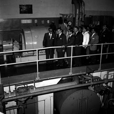Adolfo López Mateos con funcionarios escuchando el discuros de un individuo durante una visita a una industria