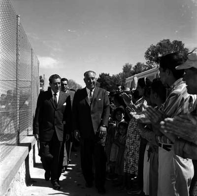 Adolfo López Mateos observando a una niña durante su visita a la escuela Revolución