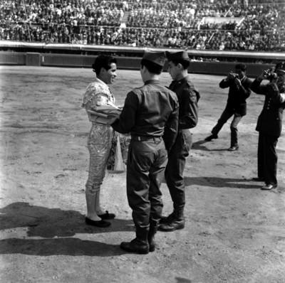 Soldados entregando una capa a un torero durante los festejo del día del soldado