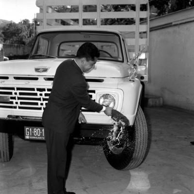 Hombre quebrando una botella en la defensa de un camión de carga