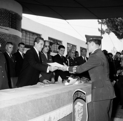 Adolfo López Mateos colocando condecoración a un militar durante una ceremoni en la escuela Superior de guerra