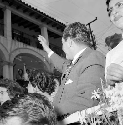 Adolfo López Mateos saluda a la gente desde un camión a su paso por las calles de Cuernavaca
