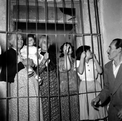 Mujeres en una ventana observando, durante la campaña de Adolfo López Mateos en Matehuala