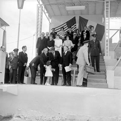 John F. Kennedy y funcionarios en un templete durante una ceremonia