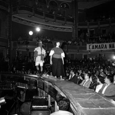 Pareja modelando trajes regionales en el homenaje a Adolfo López Mateos en el Teatro Iris