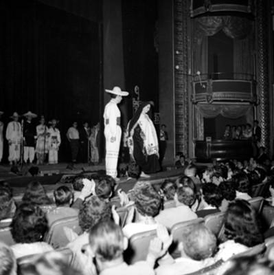 Parejas modelando trajes regionales en el teatro Iris, durante el festival en honor a Adolfo López Mateos