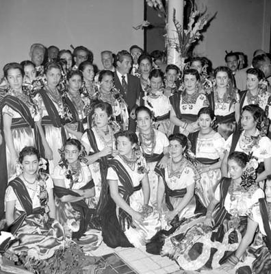 Adolfo López Mateos con bailarinas de danza canacua, en una habitación, retrato de grupo
