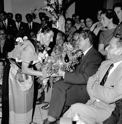 Adolfo López Mateos recibiendo flores de una mujer con vestimenta indígena, durante su campaña política por Uruapan