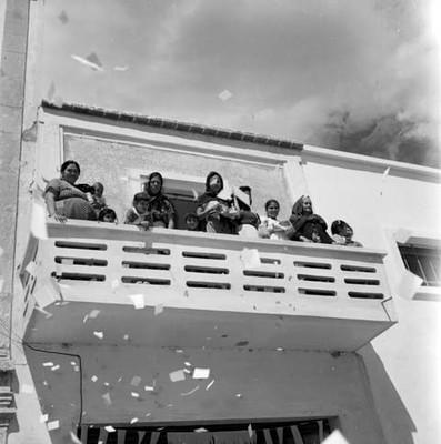 Mujeres con niños en el balcón de una casa, durante la campaña electoral de Adolfo López Mateos en Yurecuaro