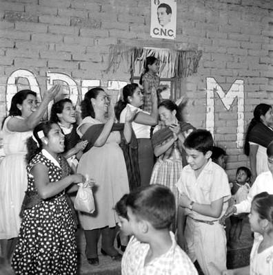 Mujeres con niños y niñas aplaudiendo durante la campaña electoral de Adolfo López Mateos, en una calle de Yurecuaro