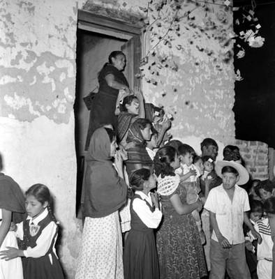 Mujeres y niños de condición humilde, arrojando confeti a fuera de una casa, durante la campaña electoral de Adolfo López Mateos en Jiquílpan