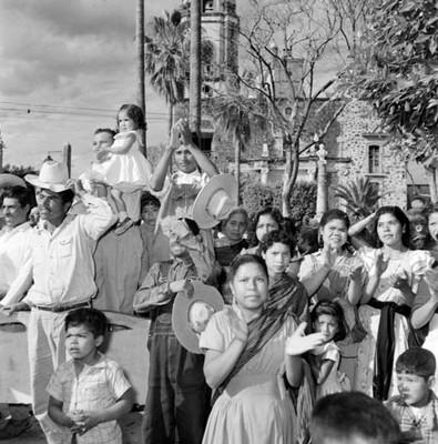 Gente de condición campesina, aplaudiendo en un jardín, durante la campaña electoral de Adolfo López Mateos en Jiquílpan