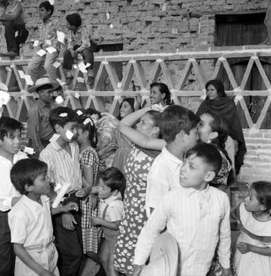 Mujer arrojando confeti a niños durante la campaña electoral de Adolfo López Mateos en Jiquílpan