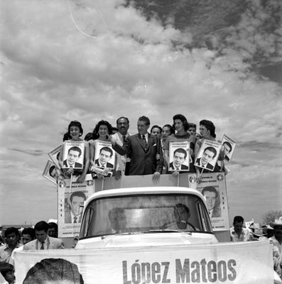 Adolfo López Mateos y edecanes en un camión, saludando a partidarios durante su campaña electoral