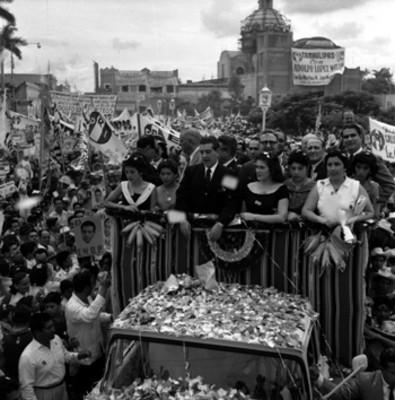Adolfo López Mateos con mujeres a bordo de un camión saludando a partidarios